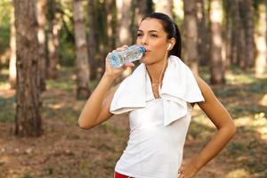 fitness linda mulher beber água de garrafas de plástico foto