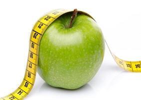 fita métrica em uma maçã verde foto