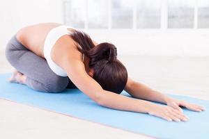 praticando ioga. mulher jovem e bonita alongamento no tapete de ioga foto