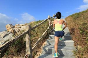 corredor de trilha de mulher jovem fitness aquecer nas escadas da montanha foto