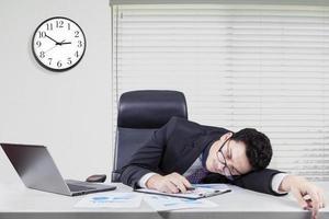 trabalhador caucasiano exausto, dormindo no escritório foto
