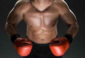 muscular jovem boxeador caucasiano usando luvas de boxe foto