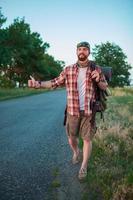 smilimg jovem turista caucasiano pedindo carona ao longo de uma estrada foto