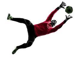 homem de goleiro de jogador de futebol caucasiano pegando a silhueta de bola foto
