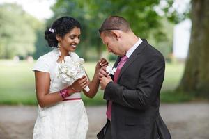 linda noiva indiana e noivo caucasiano no parque foto