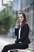 jovem empresária caucasiana do lado de fora usando phon móvel