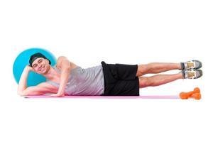 um homem caucasiano, exercitando a bola de fitness workout no studio foto