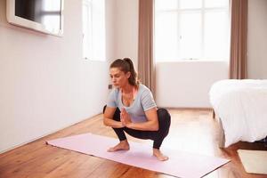 mulher fazendo yoga fitness exercícios na esteira no quarto foto