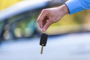 motorista latino-americano, segurando as chaves do carro, dirigindo seu carro novo foto