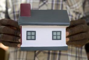 mãos africanas segurando um modelo de uma casa foto