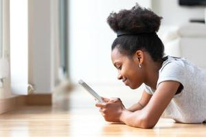 mulher afro-americana usando um tablet tátil