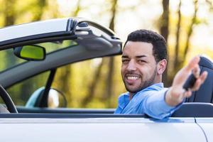 jovem piloto latino-americano preto segurando as chaves do carro foto