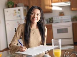 adolescente americano africano na cozinha, estudando e sorrindo para a câmera