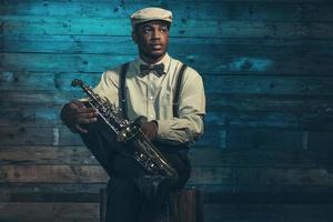 músico de jazz americano africano com saxofone. foto