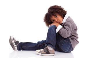 menino americano africano sentado no chão foto