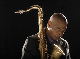 homem pensativo com saxofone, olhando para baixo foto