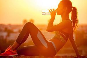 silhueta de uma jovem mulher esportiva bebendo água foto