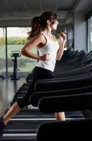 mulher correndo na esteira em uma academia vazia foto