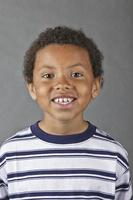 menino sorridente na camisa listrada foto