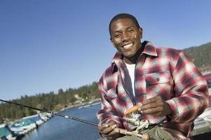 homem com vara de pescar e isca no lago foto