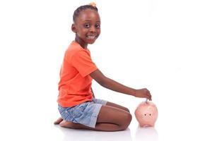 menina negra, inserindo uma nota de euro dentro de um cofrinho foto