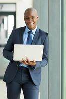 homem de negócios americano africano jovem com laptop foto