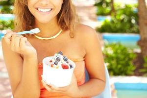 jovem americana Africano desfrutando de iogurte congelado foto