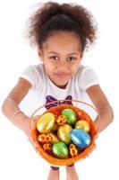 menina asiática africana segurando o ovo de éster de chocolate foto