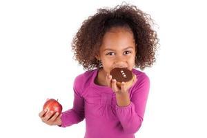 menina asiática africana comendo um bolo de chocolate