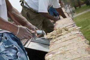 mãos de pedreiro trabalhando na parede de tijolos. foto
