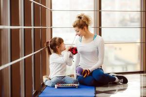 mãe e filha brincando com brinquedos no ginásio foto