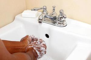 pessoa negra que lava com água e sabão foto