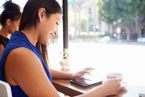 empresária usando tablet digital na cafeteria foto