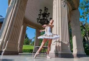 linda jovem bailarina dançando, em pé na posição de ponta. ao ar livre, primavera