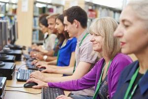 grupo de estudantes maduros trabalhando em computadores foto