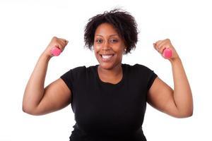 mulher negra com excesso de peso malhando com pesos-de-rosa foto