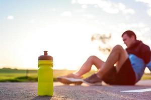 garrafa de esporte com água e corredor foto