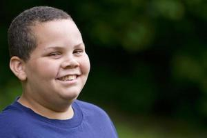 um garoto feliz com cabelos cortados rente e uma camisa azul sorri foto