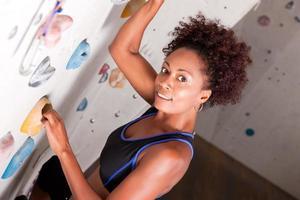 mulher na parede de escalada foto