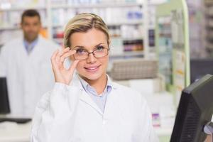farmacêutico sorridente usando o computador foto
