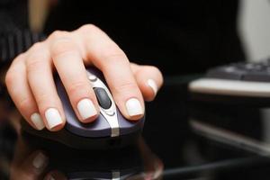 feminino mão segurando o mouse do computador foto