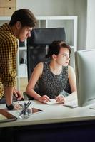 garota e cara trabalhando em um computador foto