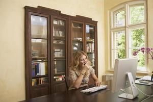 mulher bocejando sobre o computador na sala de estudo foto