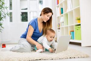 jovem atraente mãe e bebê usando o computador