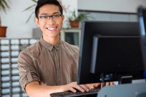estudante do sexo masculino usando computador pessoal na universidade foto