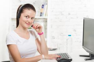 secretária bonita com um fone de ouvido e computador foto