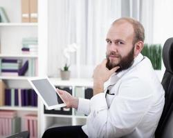 retrato eines arzt mit seinem tablet computador foto