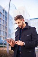 inteligente jovem empresário usando um computador tablet foto