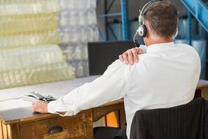 vista traseira do gerente de armazém usando o computador foto