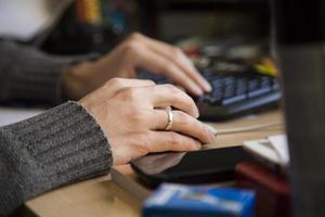 mãos de mulher tocando mouse e teclado na mesa foto